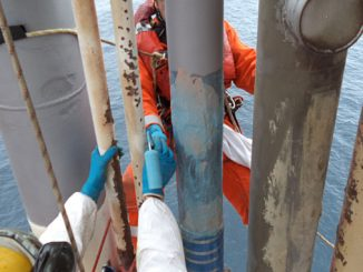 Using rollers to apply adhesive, the installation team places and secures composite sleeves on the riser