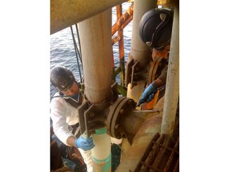 Technicians use rope access to apply a composite repair to a damaged riser on a platform offshore California